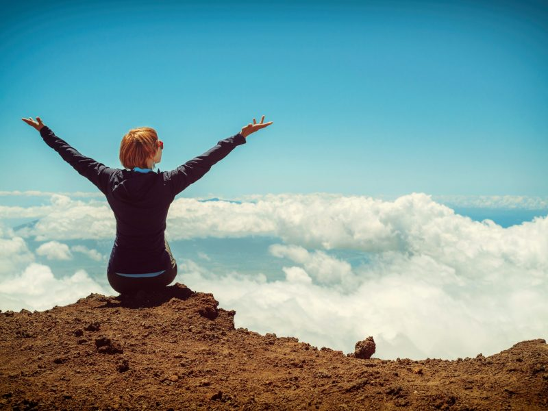 person-sitting-on-cliff-raising-up-both-hands-1439087
